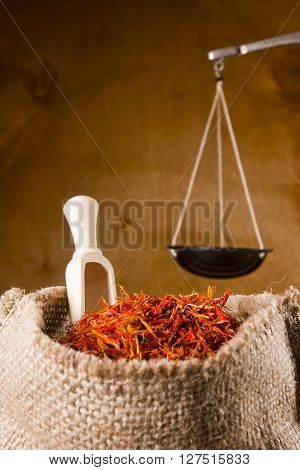 Saffron Spices in bag and scales on the wooden background