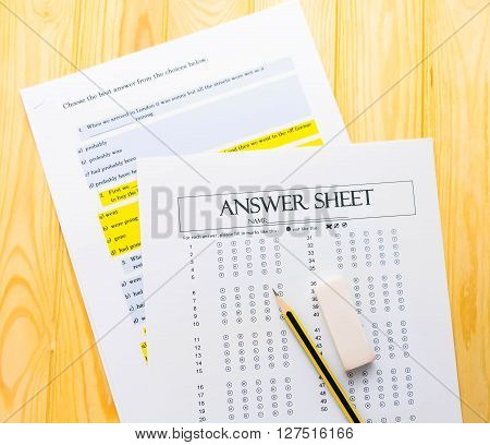 pencil and eraser on bubble answer sheet with question sheet beneath
