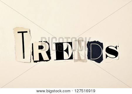 the word trends written with different letters made of clippings of newspapers and magazines, on an off-white background