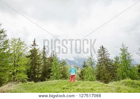 Woman wearing outdoor clothing (hardshell waterproof jacket and softshell pants), standing with trekking poles in hands and preparing for hiking in Bavarian Alps - exploring and adventure concept