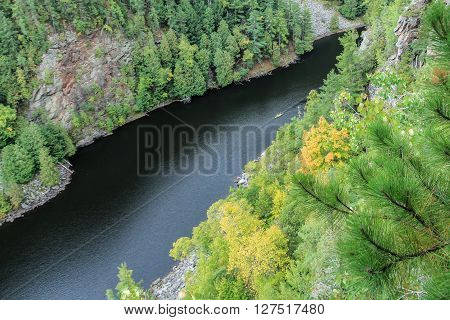 A canoe down below on the Barron River as seen from the cliffs of the Barron Canyon in Algonquin Park Ontario Canada