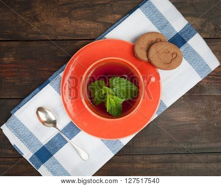Orange Tea Cup With Spoon And Cookies, Top View.
