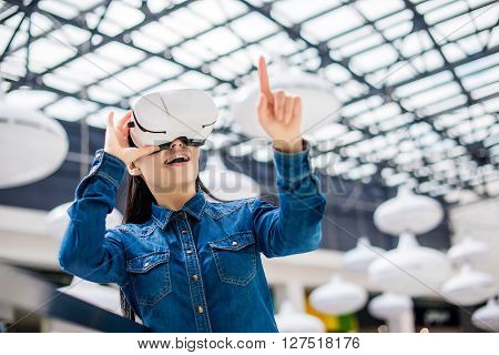 Emotional pretty woman wearing virtual reality glasses ** Note: Visible grain at 100%, best at smaller sizes