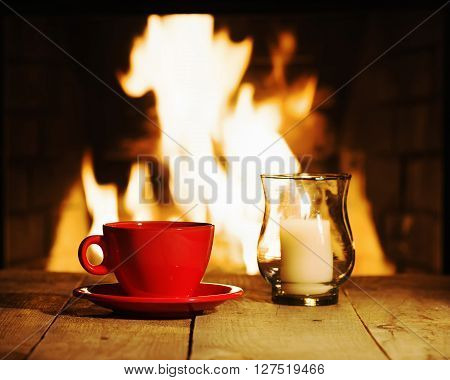 Red Cup And Candle On Wooden Table Near Fireplace.
