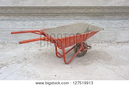 Dirty cement wheelbarrow cart at construction site with unfinished cement wall background