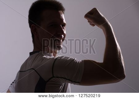 Adult male fitness demonstrates biceps. Athletic man on gray background