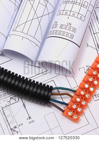 Corrugated pipe electrical cable with connection cube and rolls of electrical diagrams on construction drawing accessories for engineering work