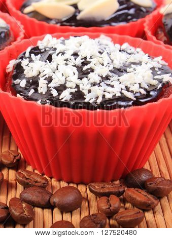 Homemade delicious fresh baked chocolate muffins with desiccated coconut and sliced almonds in red silicone cups and coffee grains on wooden background concept for dessert