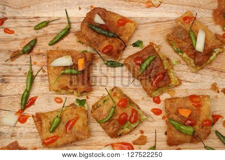 Top view of veggie martabak with chili peppers and hot souce