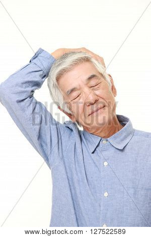 studio shot of senior man doing self neck stretch on white background