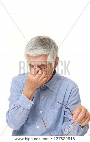 studio shot of senior Japanese man suffers from Asthenopia on white background