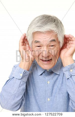 senior Japanese man with hand behind ear listening closely
