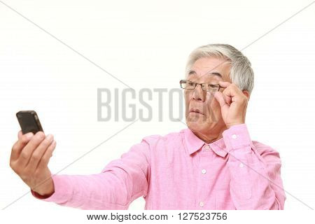 senior Japanese man with presbyopia on white background