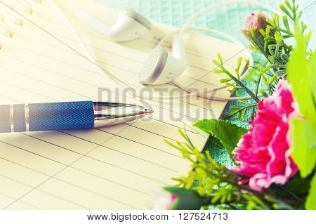 Table of composer Pen with paper and headphone and notepad on table Vintage style