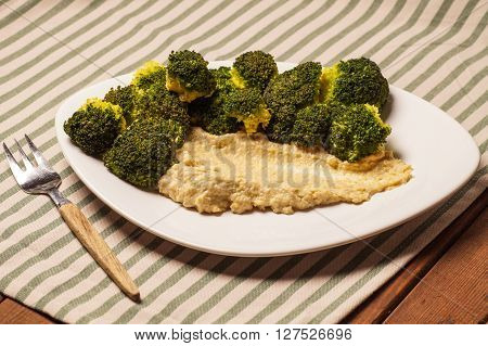 fresh organic Broccoli served with a Humus dipping