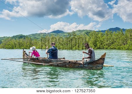 Ambatozavavy Nosy Be Madagascar - December 19 2015: Boatman a man with a girl rowing oars by outrigger canoe near the Ambatozavavy village in Nosy Be island north of Madagascar.
