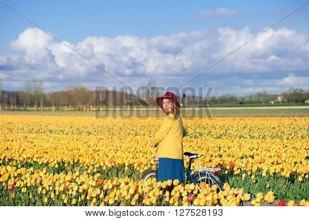 Smiling tourist standing with her bike in a yellow tulips field at sunset.
