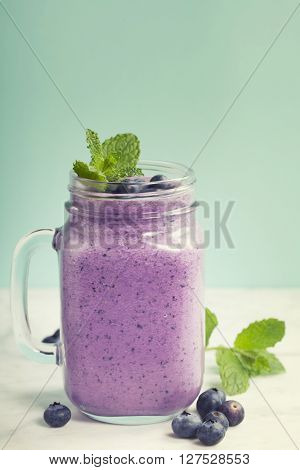 blueberry smoothie on blue background with space for text
