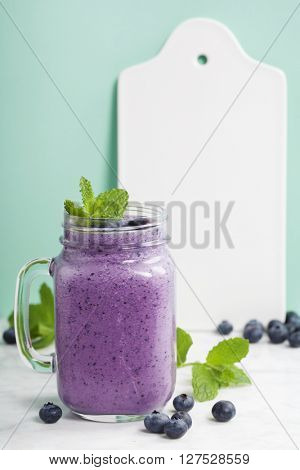 Blueberry smoothie and White ceramic serving board with space for text
