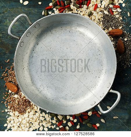 Healthy breakfast composition with space for text - oats, goji berries, banana, nuts, pumpkin and chia seeds around old empty cooking pot on rustic wooden background, top view composing