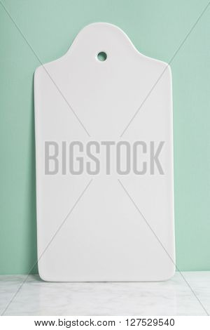 White ceramic serving board over light blue background, space for your text