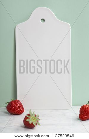 White ceramic serving board and berry over light blue background, space for your text