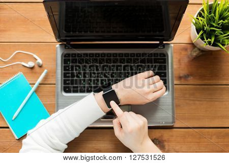 education, business, people and technology concept - close up of woman with smart watch and laptop computer on wooden table