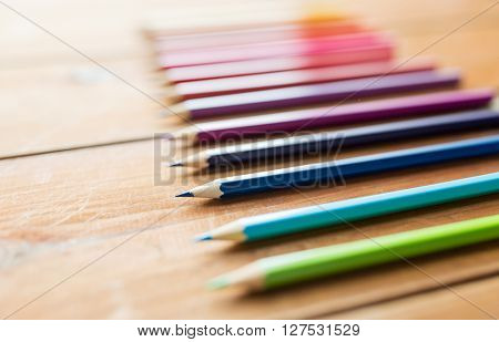 art, color, drawing, creativity and object concept - close up of crayons or color pencils on wooden table