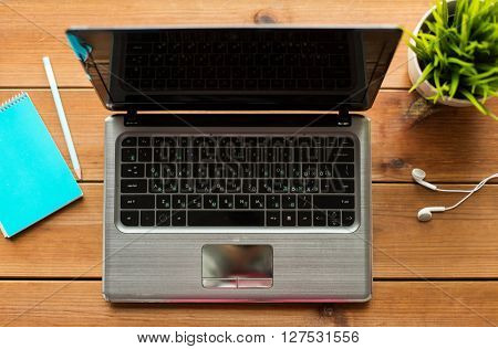 education, business and technology concept - close up of laptop computer on wooden table