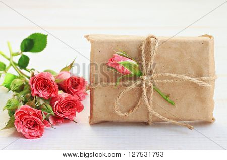 Handmade little gift box, wrapped in parchment paper, fresh roses decor. Handmade gift wrap idea.