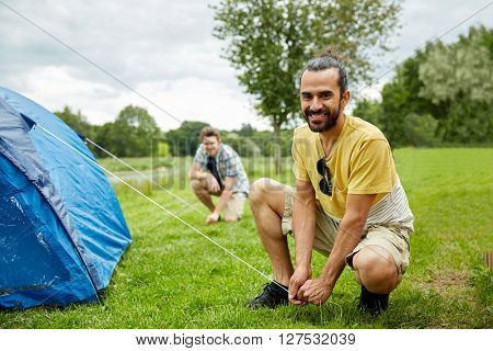 camping, travel, tourism, hike and people concept - smiling male friends setting up tent outdoors