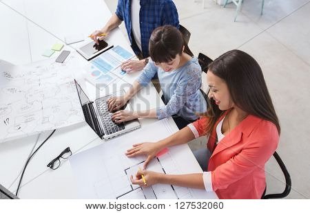 business, startup and people concept - happy creative team with laptop and blueprint at office