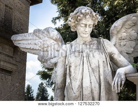 Statue of an weeping angel leaning at a grave