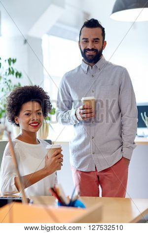 business, startup, people and drinks concept - happy latin man and african woman drinking coffee in office