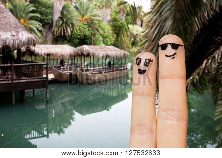 travel, tourism, summer vacation, people and body parts concept - close up of two fingers with smiley faces over exotic tropical river with boats and palm trees background
