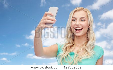 emotions, expressions and people concept - happy smiling young woman or teenage girl taking selfie with smartphone over blue sky and clouds background
