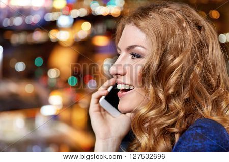 people, nightlife, technology and holidays concept - young woman calling on smartphone at night club or bar
