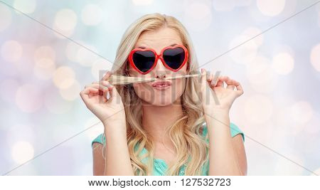 emotions, expressions, hairstyle and people concept - smiling young woman or teenage girl making mustache with strand of hair over holidays lights background