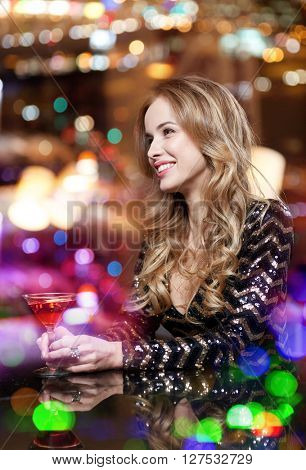 people, party, nightlife, drink and holidays concept - glamorous woman with cocktail at night club or bar