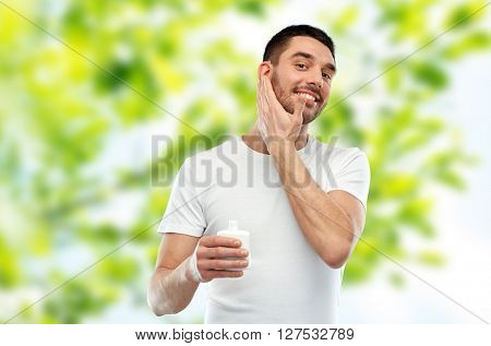 beauty, skin care, body care and people concept - smiling young man applying cream or lotion to face over green natural background