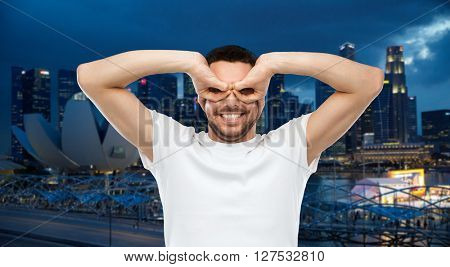 travel, tourism, fun and people concept - man making finger glasses over night singapore city background