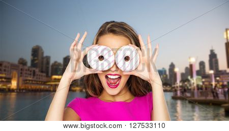 people, travel, tourism, junk food and fast food concept - happy young woman or teen girl in pink dress having fun and looking through donuts over evening city waterfront background