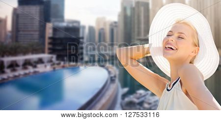 people, summer holidays, travel, tourism and vacation concept - beautiful woman in sun hat enjoying summer over dubai city background