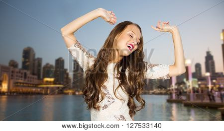 people, travel, tourism, holidays and fashion concept - happy young woman or teen girl in fancy dress with sequins and long wavy hair dancing at party over evening city waterfront background
