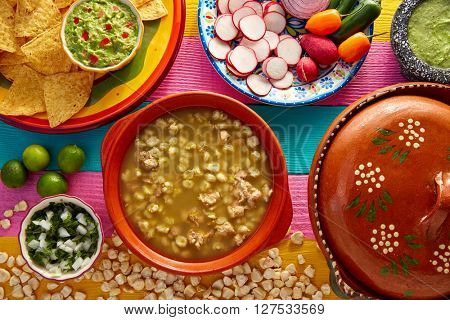 Green Pozole verde with blanco mote corn and ingredients on colorful table