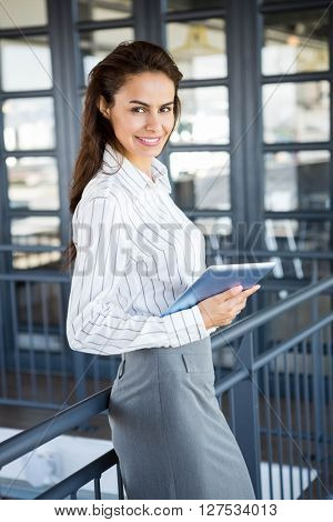 Portrait of young businesswoman holding digital tablet in office