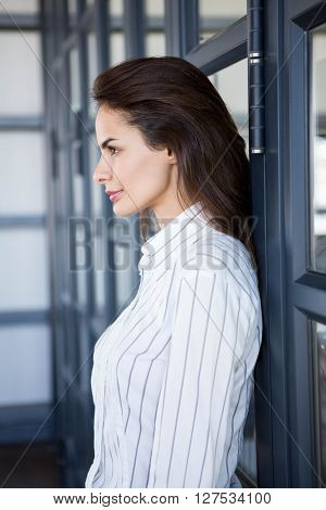 Close-up of beautiful businesswoman young leaning on office door