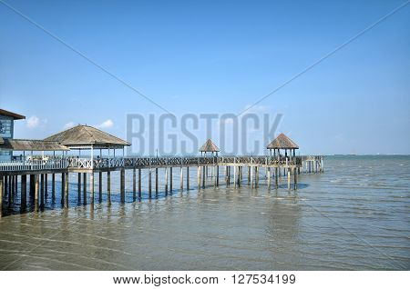 Wooden pier on the lake. In blue hue