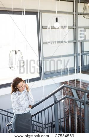 Businesswoman talking on smartphone in office