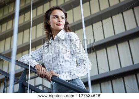 Businesswoman standing near a railing and looking away in office